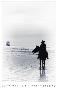 Photograph of horse and rider on a beach at Morro Bay, California
