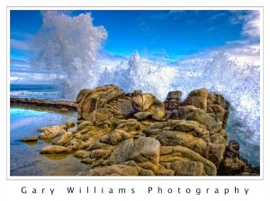 Photograph of a wave crashing against rocks at Pacific Grove, California
