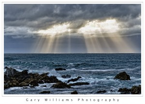Photograph of crepuscular light rays over the Pacific Ocean at Asilomar beach, California