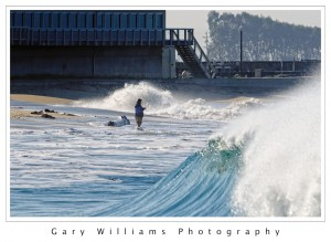 Photograph of a fisherman fishing in large waves at Moss Landing, California