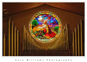 Photograph of a stained glass window surrounded by organ pipes