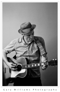 Photograph of a man wearing a pork pie hat and playing the guitar