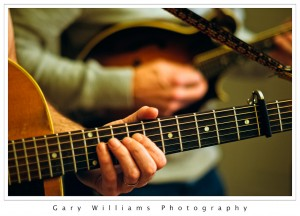 Photograph of hands playing the guitar and mandolin