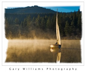 Photograph of a lone sailboat on a misty lake in Kings Canyon National Park