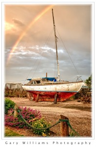 Photograph of a rainbow over a boat on dry land at Moss Landing, California