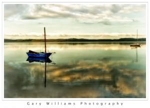 Photograph of a single boat at sunrise at Los Osos Bay