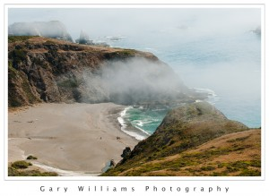 Photograph of cliffs, fog and a beach on the  northern California coast near Jenner, California
