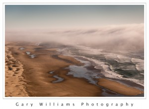 Photograph of waves, clouds, sand dunes and a beach along the southern Oregon coast