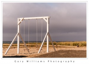 Photograph of a white swing in the backyard of a house on the beach in Neskowin, Oregon