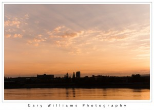 Photograph of clouds and the sun rising over the Portland Skyline and the Willamette River in Portland, Oregon