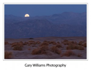 Photograph of a full moon setting at Mesquite Flats, Death Valley National Park