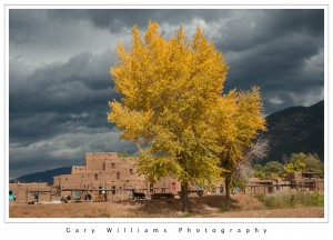 Photograph of dramatic clouds and adobe buildings in the Taos Indian Pueblo, Taos, New Mexico