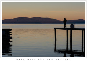 Photograph of a solitary figure watching the sunrise over Lake Tahoe from Zephyr Point, Nevada