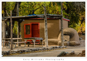 Photograph of an adobe building with a red door in the Taos Indian Pueblo, Taos, New Mexico