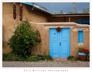 Photograph of an adobe buildings with a blue door and chile ristras near Rancho De Taos, New Mexico