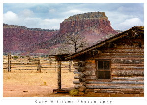Photograph of an old cabin and redrock cliffs at Ghost Ranch near Albiquí, New Mexico