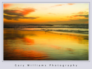 Photograph of the sun setting at Moss Landing Beach in Moss Landing, California