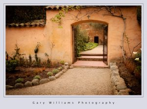Photograph of a path and archway at the Carmel Mission at Carmel, California
