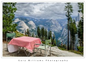 Photograph of a picnic table and chairs overlooking Half Dome at Yosemite National Park, California