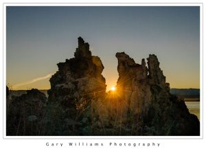 Photograph of the sun rising behind tufa columns at Mono Lake, California